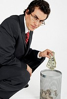 Portrait of a businessman throwing paper currency into a wastepaper basket