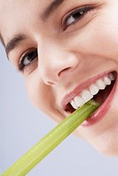 Portrait of a young woman biting into a celery stick