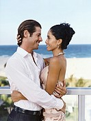 Couple Stand Embracing Face-to-Face on a Balcony Above a Beach
