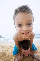 Close up of a Boy on a Beach Carried by His Father