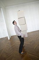 Man Standing in an Empty Room Carrying a Stack of Cardboard Boxes