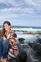 Young woman sitting on rock on shoreline, wrapped in blanket, smiling