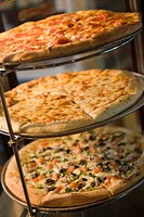 Various pizzas on stand, close-up