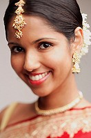 Woman in wearing Indian jewellery, smiling at camera