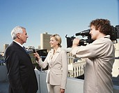 Businessman being interviewed by female reporter with cameraman