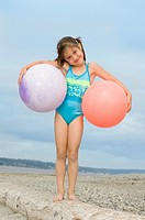 Girl 4-6 standing atop driftwood, holding two beach balls, portrait