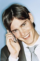 Young businessman using mobile phone, smiling, portrait, close-up