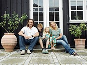 Family sitting on steps of house, smiling, portrait