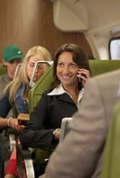 Businesswoman travelling on train using mobile phone, smiling