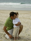 Father and son 3-4 relaxing on beach