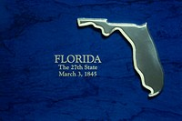 ´This is a silver map of the state of Florida  It is against a blue background  It reads, Florida, the 27th State, March 3, 1845 which is the date it ...