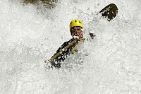 Man white-water kayaking surrounded by spray