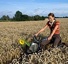 Woman riding bicycle on wheat field