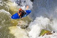 Young man kayaking over waterfall, elevated view