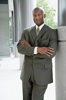 Mature business man leaning against pillar, portrait