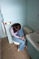 Young woman sitting in her bathroom