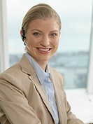 Businesswoman wearing headset, smiling, portrait