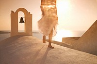 Greece, Santorini, Oia, woman walking, low section, sunset