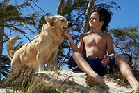 Boy 10-12 sitting beside golden retriever, smiling