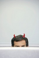 Mature businessman with devil horns sitting in cubicle, high section
