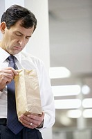 Mature businessman looking in paper lunch bag
