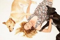 Mature woman lying between two Labrador retrievers, elevated view
