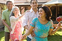 Family dancing conga in garden, young woman holding maraca, smiling
