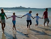 Three-generation family with two children 7-10 holding hands on beach