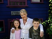´Senior woman and grandchildren 6-7, 8-9 posing in front of miniature house in garden, portrait´