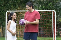 Mature man holding a football and talking to his daughter