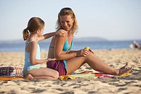 Daughter 7-9 putting sunscreen on mother on beach