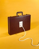 Briefcase with electric plug socket on yellow background still life