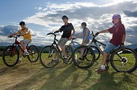 Four teenagers 12-14 riding bicycles, portrait