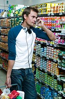 Man shopping in supermarket, using mobile phone