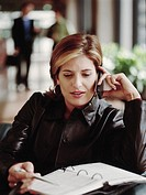 Woman sitting in lobby talking on mobile phone