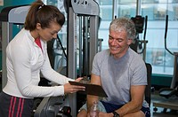 Person trainer and mature man working out in gym, close-up