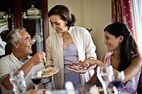 Mother bringing dishes to father and adult daughter at dining table