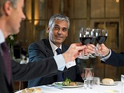 Businessmen sitting at restaurant table, toasting