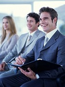 Businessman writing in folder in meeting, smiling