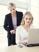 Mature businesswoman with young woman using laptop