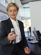 Mature businesswoman using mobile phone in office