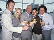 Businessmen and women holding champagne, smiling, portrait