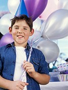 Boy 8-10 holding balloons, smiling, portrait