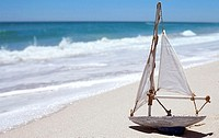 White toy sailing boat on sandy beach near water's edge, side view, sea in background