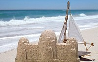 White toy sailing boat behind sandcastle on beach near water's edge, sea in background