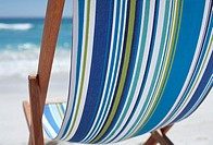 Stripy blue deckchair on sandy beach, mid-section, close-up, rear view