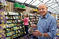 Senior couple shopping in garden centre, man holding flower bulbs, smiling, side view, portrait