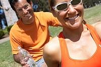 Couple sitting on grass in park, smiling, man holding water bottle, close-up, portrait tilt