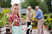 Girl 7-9 holding watering can in garden centre, smiling, portrait, grandparents in background
