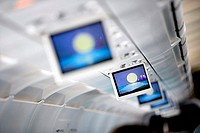 Row of blue visual screens in airplane cabin aisle differential focus